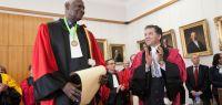 Abdou Diouf, en toge, tient un diplôme. Jacques Bahi applaudit. Derrière, un certain nombre de personnes en toge applaudissent également.