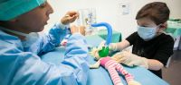 Une petite fille porte un masque et des gants en latex. Elle applique un masque et un tuyau sur la bouche de sa poupée pendant qu'un étudiant en médecine lui explique quelque chose.