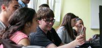 Un groupe d'étudiants travaillent ensemble en riant.