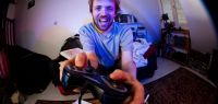 Un homme tient une manette de jeux vidéos.