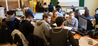 Plan large sur une salle où travaillent des groupes d'étudiants.