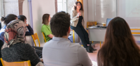 Un groupe d'étudiants dans une salle, devant eux, une femme en train de parler.
