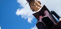 Vue en contre plongée d'un personnage sculpté qui lit un livre sur un ciel bleu