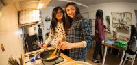 Cinq jeunes taiwanaises en train de préparer des galettes dans une cuisine.