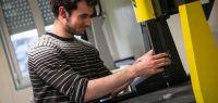 Un étudiant tient un appareil qui ressemble à une fraiseuse.