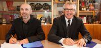 Les mains de deux personnes en costume lors d'une signature officielle.