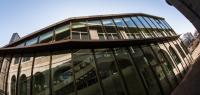 Vue extérieure de la MSHE Ledoux avec des vitres dans lesquelles se reflètent des arcades.