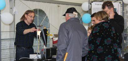 Un chercheur présentant un dispositif expérimental sur un stand avec des gens de dos.
