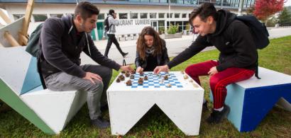trois étudiants en train de jouer aux échecs sur du mobilier d'extérieur en carton.