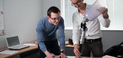 Deux étudiants examinent une sorte de prothèse de jambe.