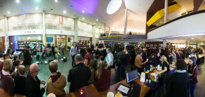 Vue panoramique de l'intérieur d'une bibliothèque pleine de monde, avec des gens debout et des musiciens.