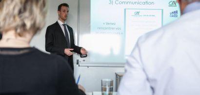 Un étudiant en costume cravate fait une présentation. Deux membres du jury sont de dos.
