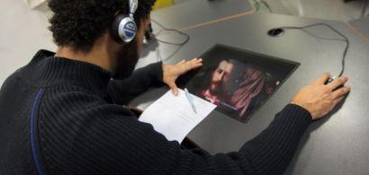 Un homme de dos avec un casque regarde un écran et une souris
