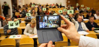Un amphithéâtre où les gens brandissent des papiers, devant des mains tiennent un téléphone portable.