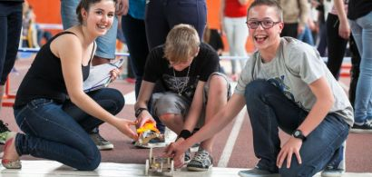 Trois collégiens rient accroupisd errirèe leur robot.
