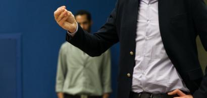 Un étudiant en costume parle devant un public