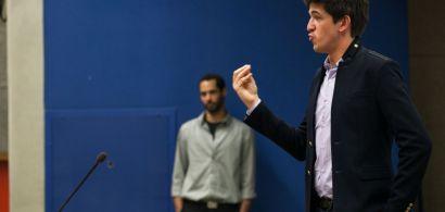 Un homme parle devant un public, son concurent en arrière plan.