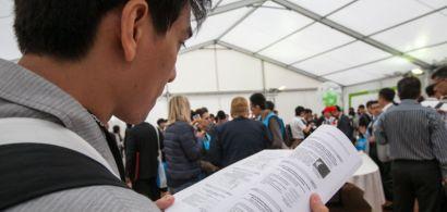 Un homme asiatique de dos feuillette un document scientifique. Beaucoup de monde debout en arrière-plan.