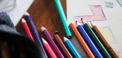 Des crayons de couleur posés sur un dessin d'enfant.