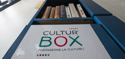 Une étagère avec une étiquette marquée Cultu'Box