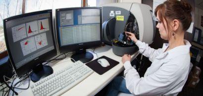 Une personne en train de manipuler un cytomètre de flux.