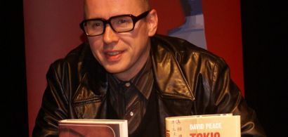 Portrait de David Peace devant ses deux livres.