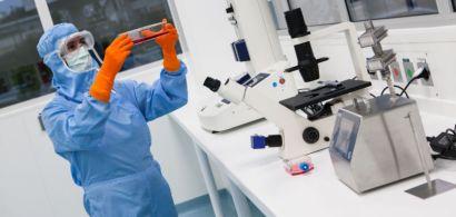 Une femme en combinaison bleue et gants oranges tient une boite avec un liquide rouge, devant une paillasse où se situent sifférents appareils dont un gros microscope.