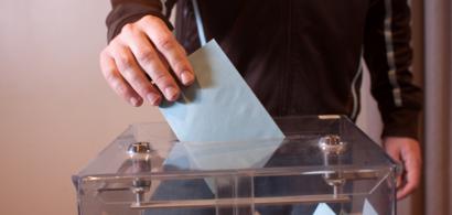 Une main dépose une enveloppe dans une urne