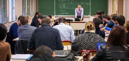 Une salle de classe avec de nombreux étudiants penchés sur leurs copies et au tableau Guy Labarre qui donne cours.