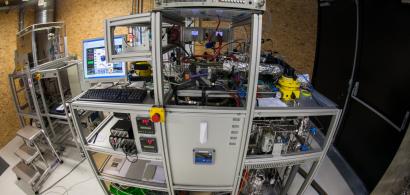 Un gros banc d'essai avec un écran et clavier d'ordinateur, et de nombreux tuyaux et appareillages.