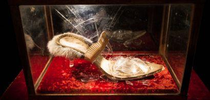 Chaussure en verre brisé dans une vitrine sur un coussin de velours rouge.
