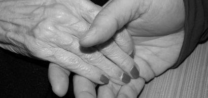Une main maigre de personne âgée tenue par une autre main