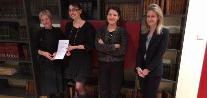 Quatre femmes debout tenant une convention de partenariat