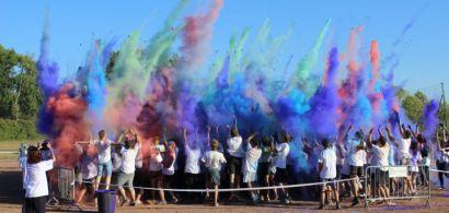 Un groupe de jeunes gens en tee shirt blanc de dos. Au dessus d'eux, une explosion de poudre colorée.