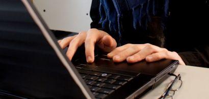 Un jeune homme devant un clavier d'ordinateur.
