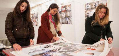 Trois étudiantes de la licence professionnelle METI en train d'examiner des grands tirages photos lors de l'accrochage.