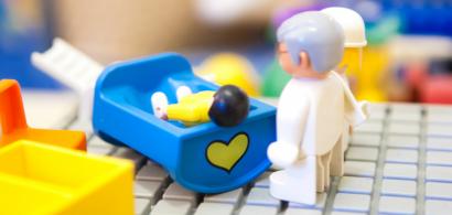 Des playmobils représentant un enfant couché sur un lit et deux adultes à son chevet.
