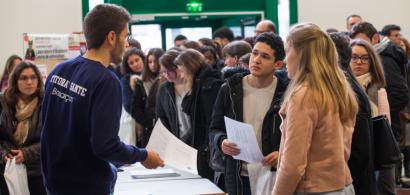Un tuteur renseigne des étudiants dans la foule des journées portes ouvertes dans le hall de l'UFR Santé.