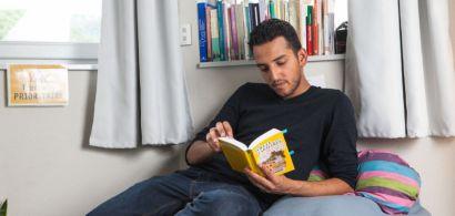 Un étudiant en train de lire un livre sur un lit.