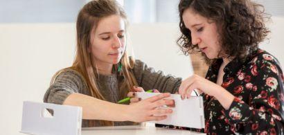 Deux étudiantes en train de positionner les éléments d'un tabouret en carton.