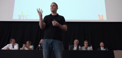 Un jeune homme parle sur une scène.