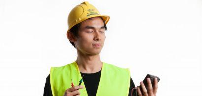 Un étudiant avec un casque de chantier et un gilet jaune fluo
