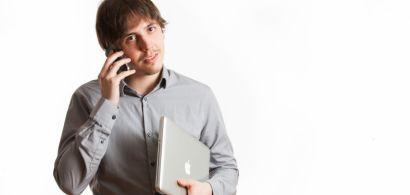 Un jeune homme en train de téléphoner et tenant un ordinateur portable