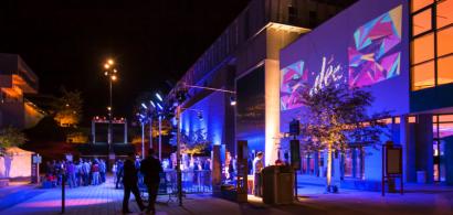 """Vue extérieure du parvis de la faculté de médecine de Besançon, de nuit, avec des éclairages bleu violets. Le mot """"idées"""" et des formes géométriques sont projetées sur la façade. Il y a du monde sur la place."""