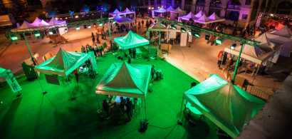Vue plongeante sur le site de l'Arsenal lors de la nuit des chercheurs, avec des tentes dans une lumière verte et des visiteurs.