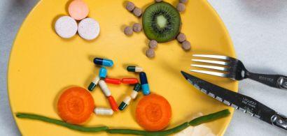 Dans une assiette, un vélo dessiné avec des fruits et légumes et des comprimés et gélules.