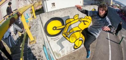 Un jeune homme suspendu dans les airs à côté d'un mur dans un décor urbain.