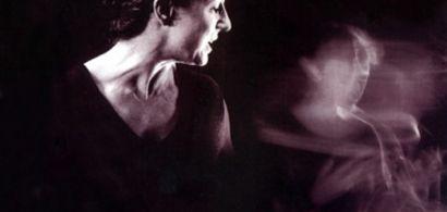 Une femme en noir et blanc avec une silhouette floue derrière elle.