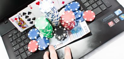 Des jetons de poker, cartes à jouer et billets posés sur un ordinateur portable