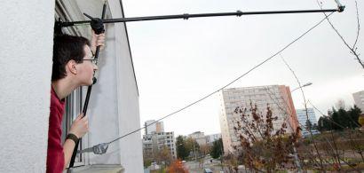 Un jeune homme penché à la fenêtre tient une perche au bout de laquelle est fixée un micro dans un environnement urbain.